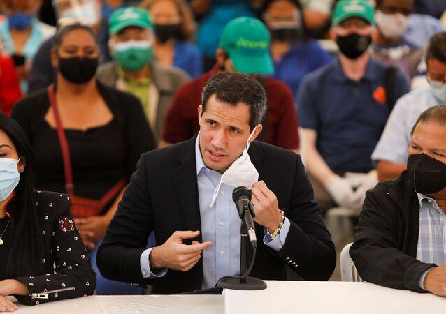 O líder da oposição venezuelana Juan Guaidó remove sua máscara ao chegar a uma entrevista coletiva em Caracas, Venezuela, em 3 de março de 2021