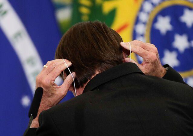 Em Brasília, o presidente Jair Bolsonaro (sem partido), aparece de costas enquanto coloca uma máscara de proteção contra a COVID-19 durante coletiva, em 25 de março de 2021