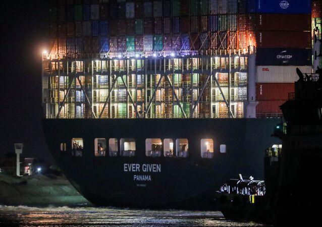 No Egito, o navio cargueiro Ever Given, encalhado no canal de Suez, é visto durante a noite, em 27 de março de 2021