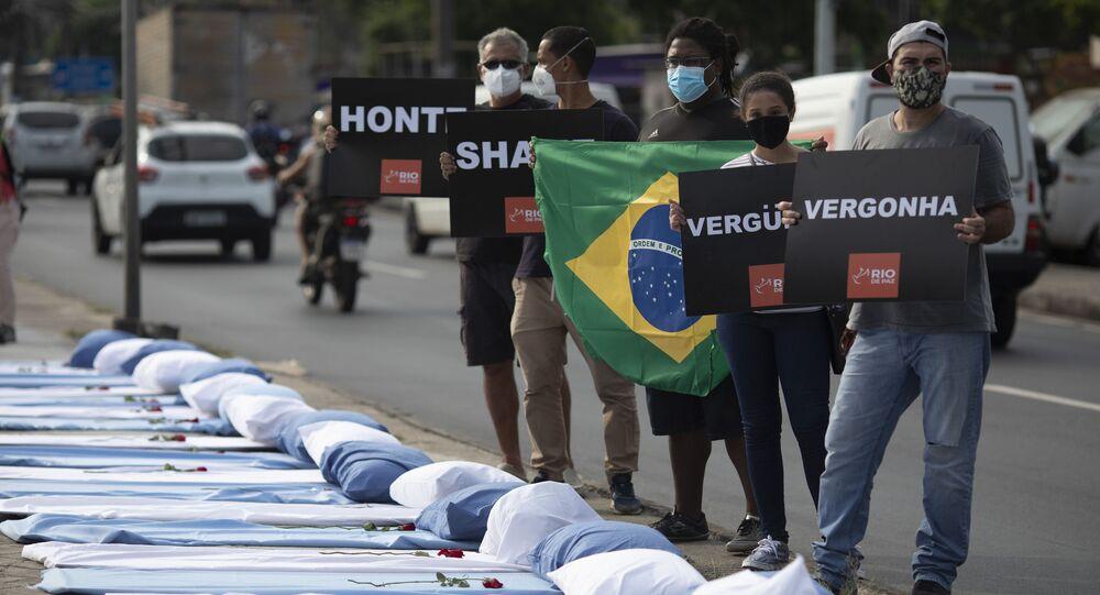 Manifestantes seguram cartazes com mensagem vergonha próximo de leitos simbolizando as vítimas da COVID-19 no Rio de Janeiro durante protesto antigovernamental, 24 de março de 2021