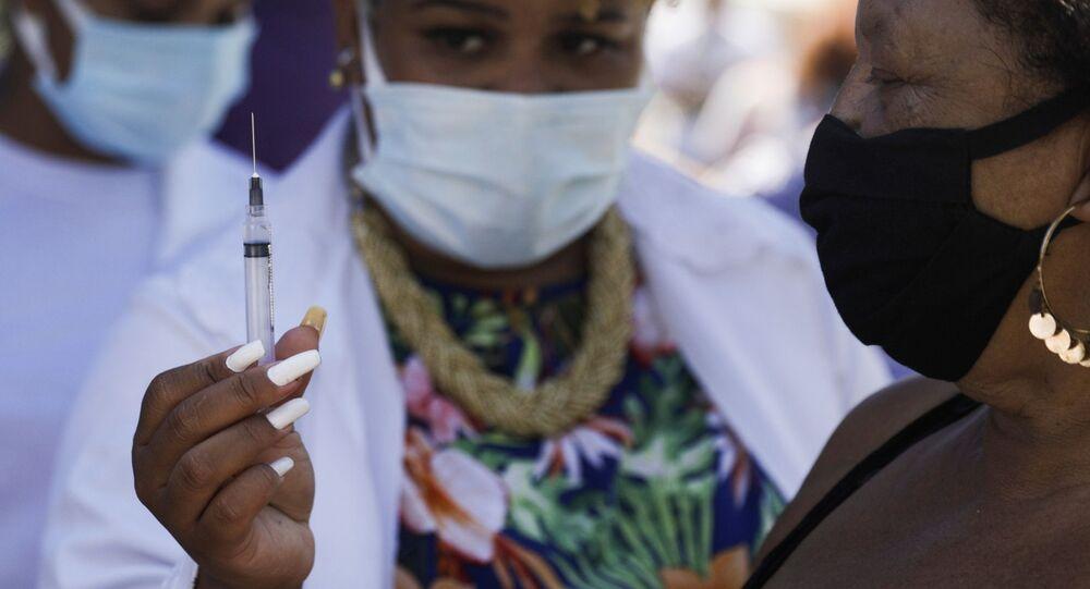 Enfermeira mostra seringa para mulher em Duque de Caxias, no Rio de Janeiro, em 29 de março de 2021