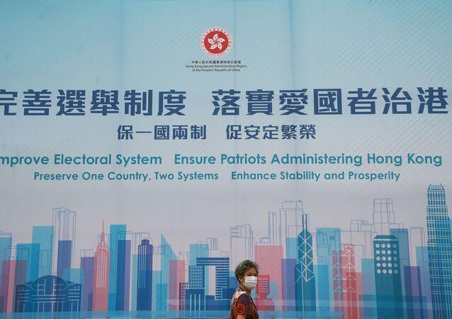 Mulher passa por anúncio governamental de promoção das reformas eleitorais de Hong Kong após aprovação do plano da reforma pelo Parlamento chinês, Hong Kong, China, 30 de março de 2021