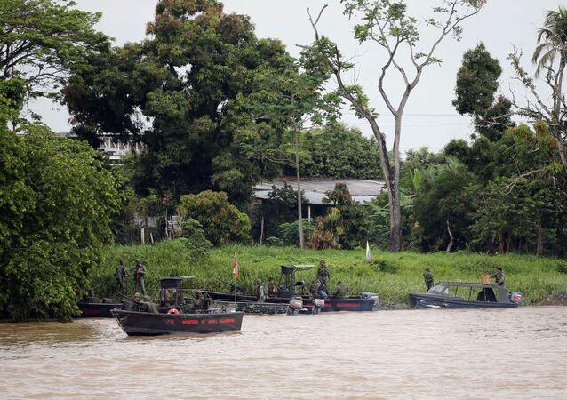 Soldados venezuelanos patrulham o rio Arauca na fronteira entre a Colômbia e Venezuela, visto da cidade de Arauquita, Colômbia, 28 de março de 2021
