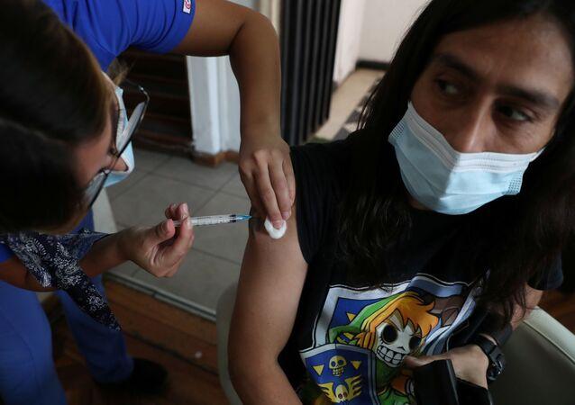 Em Santiago, no Chile, um profissional de saúde aplica uma dose da vacina CoronaVac contra a COVID-19, em 24 de março de 2021