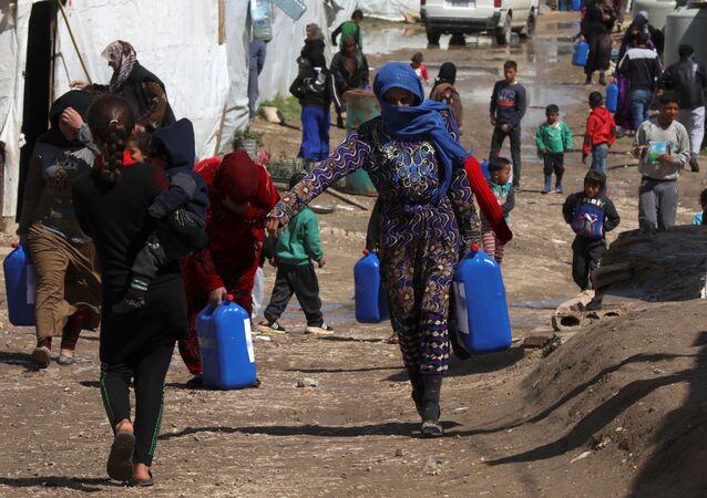 No vale de Bekaa, no Líbano, refugiados sírios carregam galões em um assentamento, em 12 de março de 2021