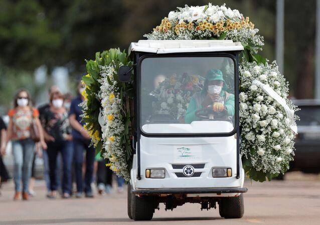 Trabalhador dirige carro com flores e caixão de pessoa falecida por COVID-19, no cemitério Cemitério Campo da Esperança, em Brasília, no Brasil, no 11 de março de 2021