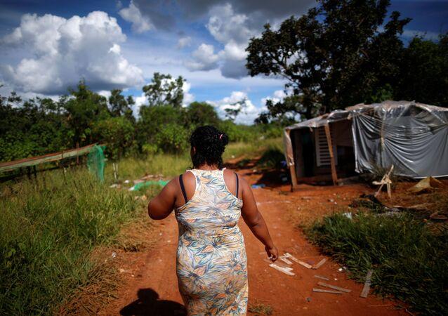 Mulher caminha perto de barraco onde vive nas proximidades do Palácio do Planalto, em Brasília