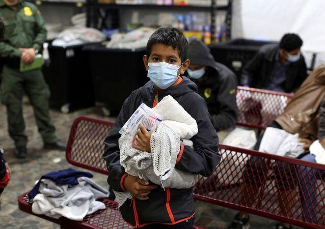 Pequeno migrante aguarda na fila para tomar banho em uma instalação do Departamento de Segurança Interna dos Estados Unidos, a principal instalação de custódia para crianças desacompanhadas no Texas