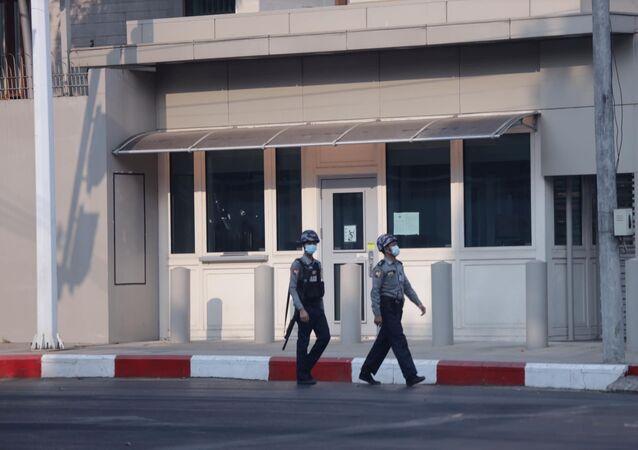 Policiais caminham em frente ao Centro Americano de Rangum em Mianmar, que foi alvo de disparos