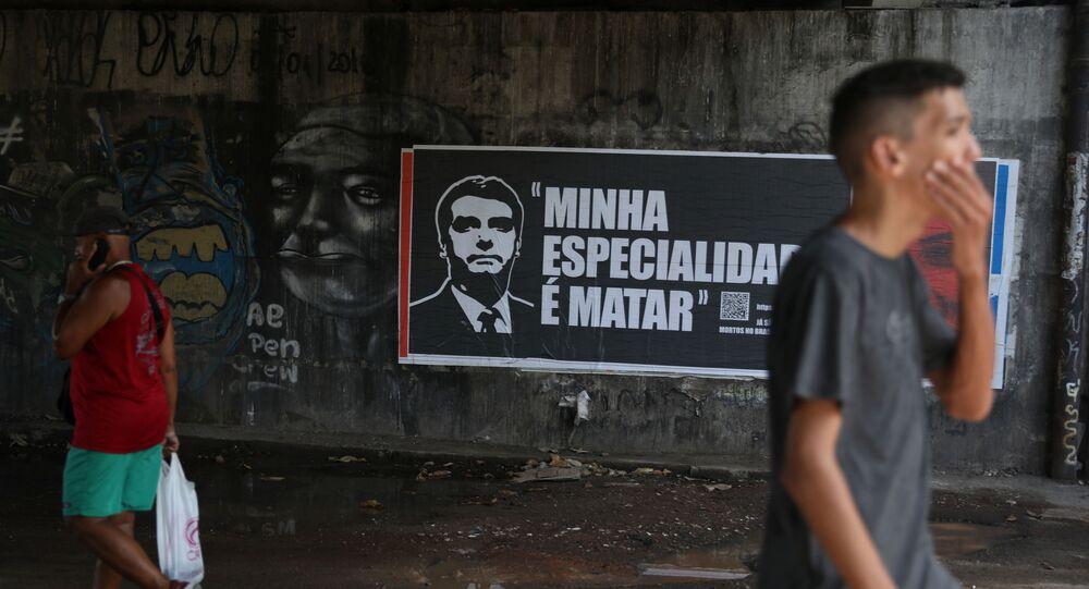 Pessoas caminham na frente de um cartaz com a imagem do presidente do Brasil, Jair Bolsonaro, durante a pandemia de COVID-19, no Rio de Janeiro, 30 de março de 2021