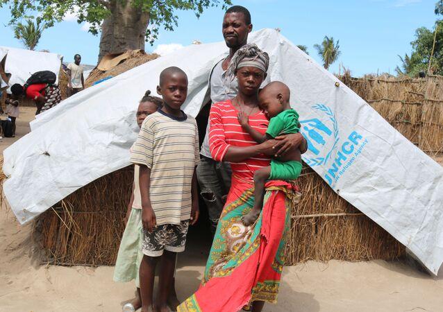 Uma mulher, chamada Elsa pelo grupo de ajuda baseado no Reino Unido Save the Children, está com a família em um campo de deslocados na província de Cabo Delgado, no norte de Moçambique, em 26 de janeiro de 2021.