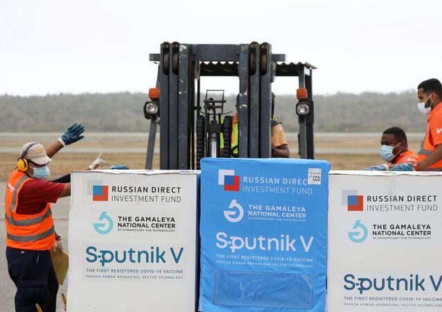 Trabalhadores observam o embarque da vacina russa Sputnik V no aeroporto de Caracas, Venezuela, 29 de março de 2021.