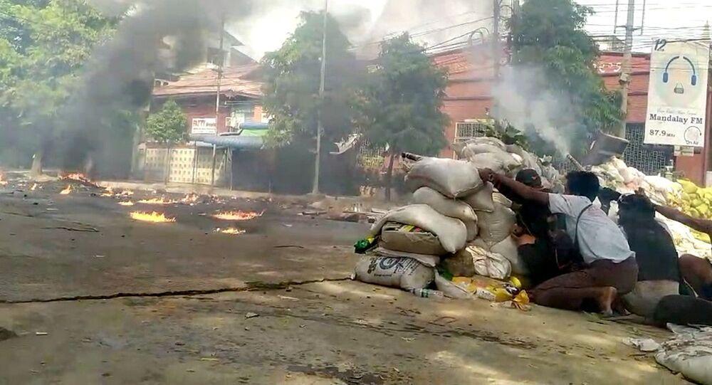 Manifestantes se protegem atrás de barricadas durante protesto reprimido pelos militares, em Mandalay, Mianmar, em 27 de março de 2021