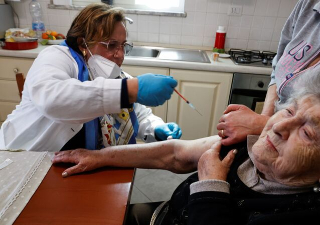 Em Nápoles, na Itália, uma profissional de saúde aplica uma vacina contra a COVID-19 em uma idosa, em 30 de março de 2021