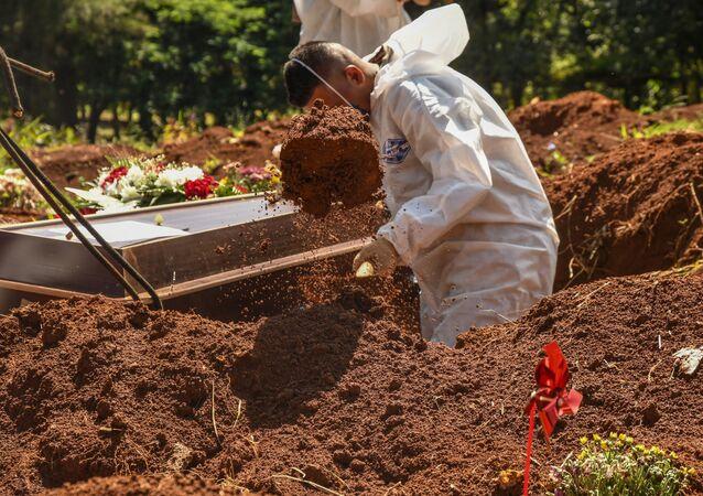 Sepultadores trabalham em covas abertas no cemitério de Vila Formosa, na capital paulista. Número de enterros voltam a crescer nos cemitérios paulistanos