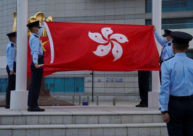 Policiais seguram as bandeiras de China e Hong Kong durante a cerimônia de abaixamento de bandeira, em Hong Kong, China, 30 de março de 2021