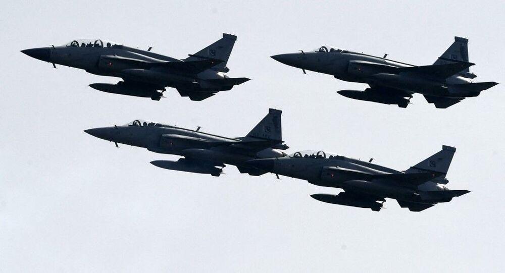 Caças da Força Aérea do Paquistão voam em formação durante desfile militar