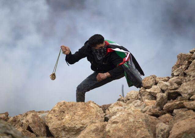 Um manifestante palestino usa uma funda para atirar pedras contra soldados israelenses durante um protesto contra os assentamentos israelenses, na vila de Mughayer, perto da cidade de Ramallah, na Cisjordânia,15 de janeiro de 2021