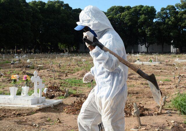 Funcionário de cemitério no Rio de Janeiro durante enterro de vítima da COVID-19.