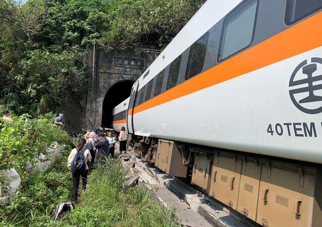 Pessoas caminham ao lado do trem que descarrilou em um túnel a norte de Hualien