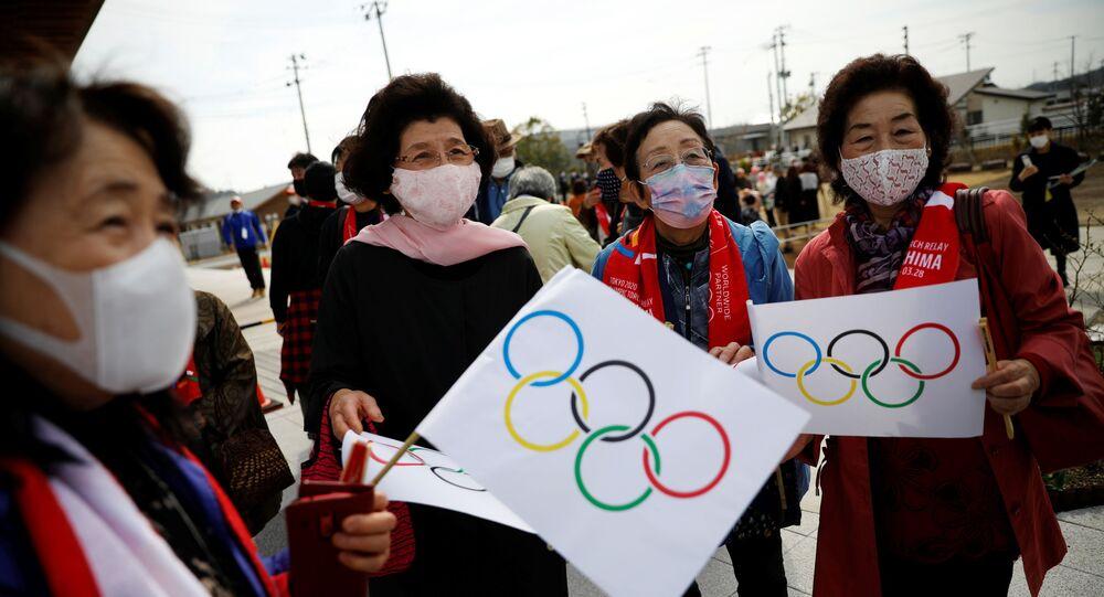 Pessoas com bandeiras olímpicas no percurso de passagem da Tocha Olímpica Tóquio 2020, Japão, 25 de março de 2021