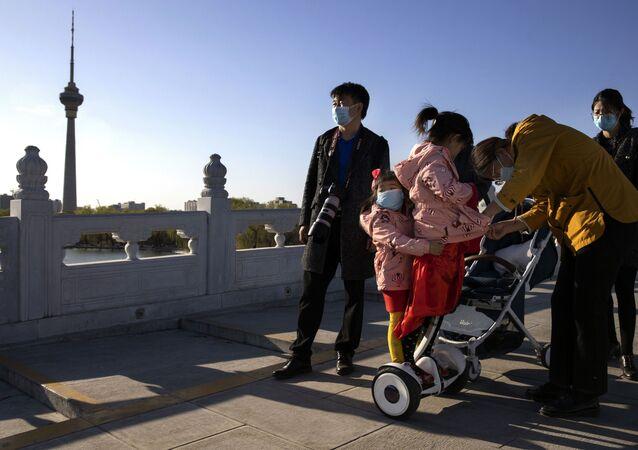 Família usa máscara e aproveita dia de sol em parque de Pequim