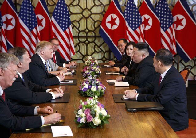 O ex-presidente dos EUA, Donald Trump, terceiro a partir da esquerda, fala com o conselheiro de Segurança Nacional John Bolton, à esquerda, e o secretário de Estado, Mike Pompeo, segundo a partir da esquerda durante uma reunião com o líder norte-coreano Kim Jong-un em 28 de fevereiro de 2019