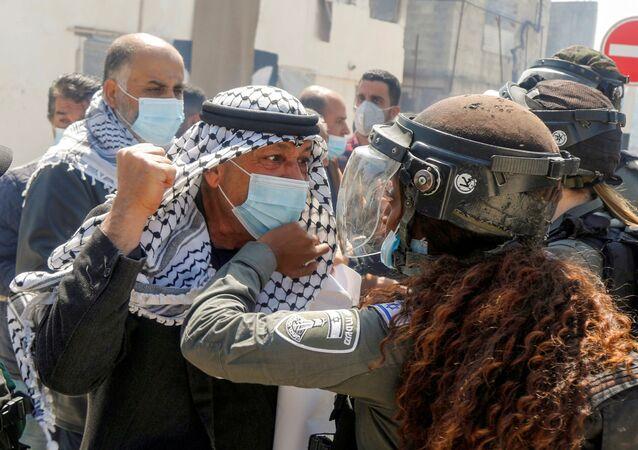 Manifestante palestino briga com uma guarda de fronteira israelense durante protestos no Dia da Terra Palestina em Sebastia, na Cisjordânia, 30 de março de 2021