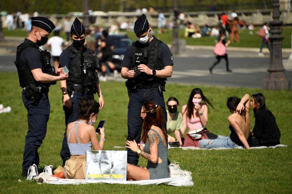 Policiais franceses verificam documentos das pessoas que descansam no gramado em Paris, França, 31 de março de 31