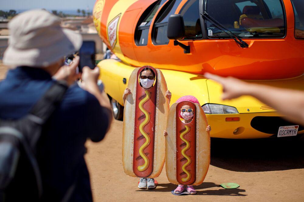 Crianças viram cachorro-quente durante evento ao lado de famoso carro em forma de hot dog Oscar Myer Wienermobile em Carlsbad, EUA