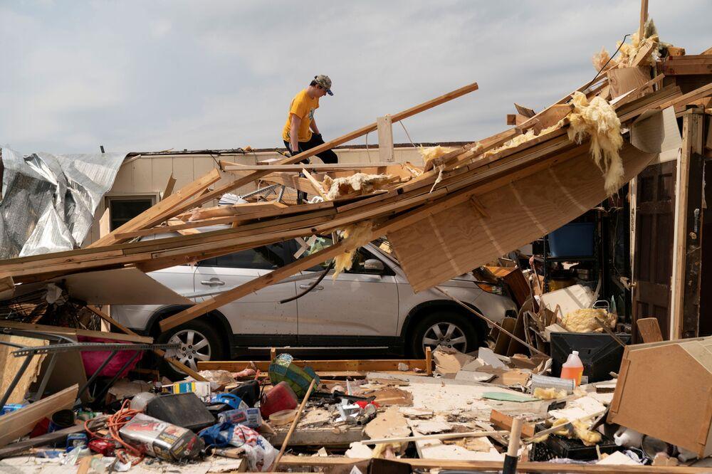 Homem avalia destruições em casa de sua bisavó um dia após a passagem de uma série de tornados no estado de Alabama, EUA, 26 de março de 2021
