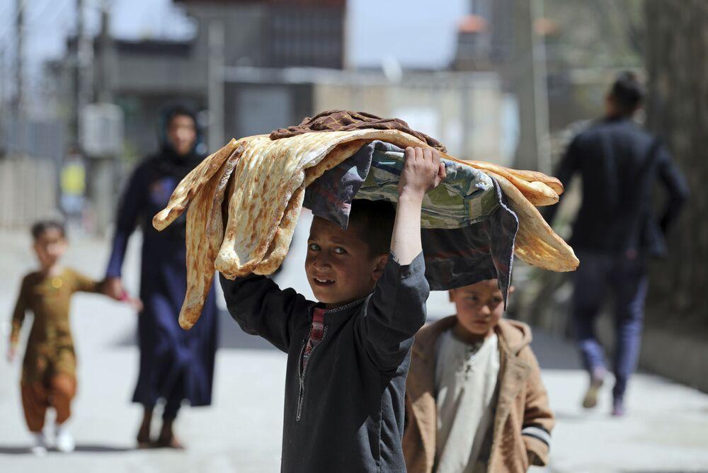 Menino afegão carrega pão na cabeça em Cabul, Afeganistão, 29 março de 2021