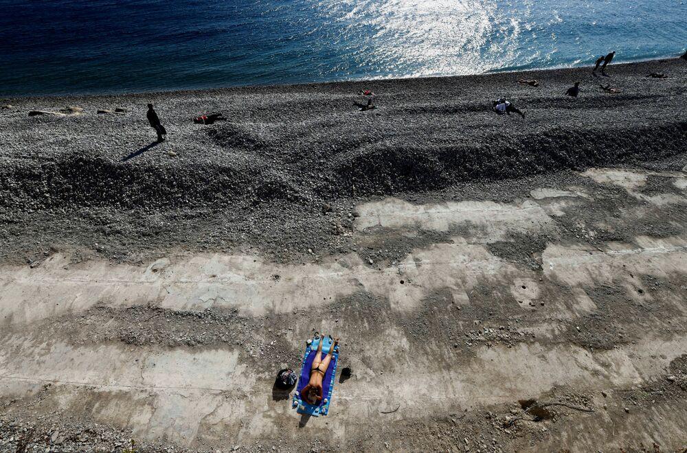 Mulher toma banhos de sol na praia, em Nice, durante o terceiro lockdown em França, 27 de março de 2021