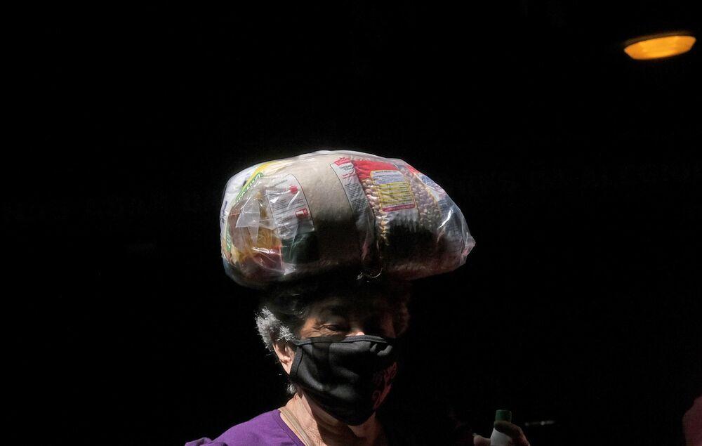Residente da favela da Rocinha carrega um saco de comida após receber doações do Instituto Abelhas do Amor, 1º de abril de 2021