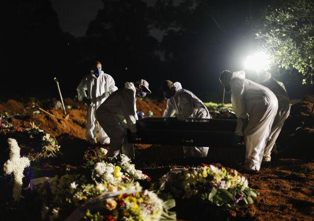 Em São Paulo, coveiros realizam enterros noturnos devido à crescente demanda em meio à pandemia da COVID-19, em 3 de abril de 2021