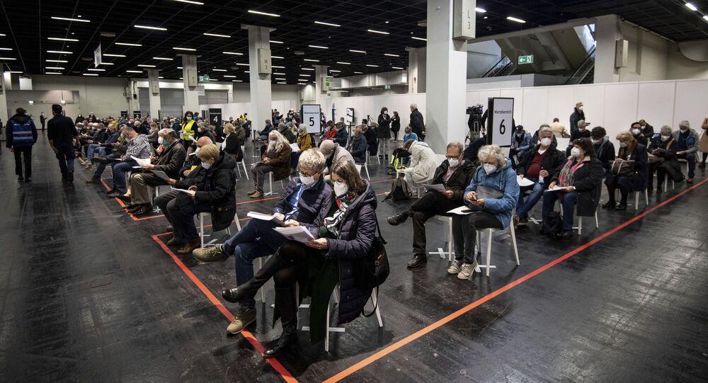 Em Colônia, na Alemanha, pessoas esperam de máscara em um centro de vacinação contra a COVID-19, em 4 de abril de 2021