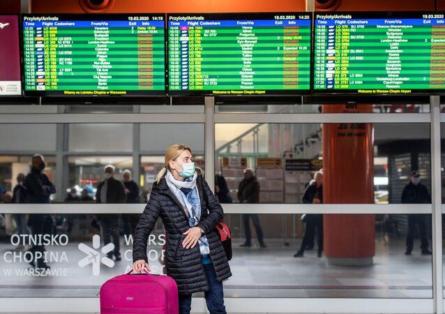 Em Varsóvia, na Polônia, uma viajante de máscara de proteção contra a COVID-19 caminha no saguão de desembarque do aeroporto Chopin, em 19 de março de 2020