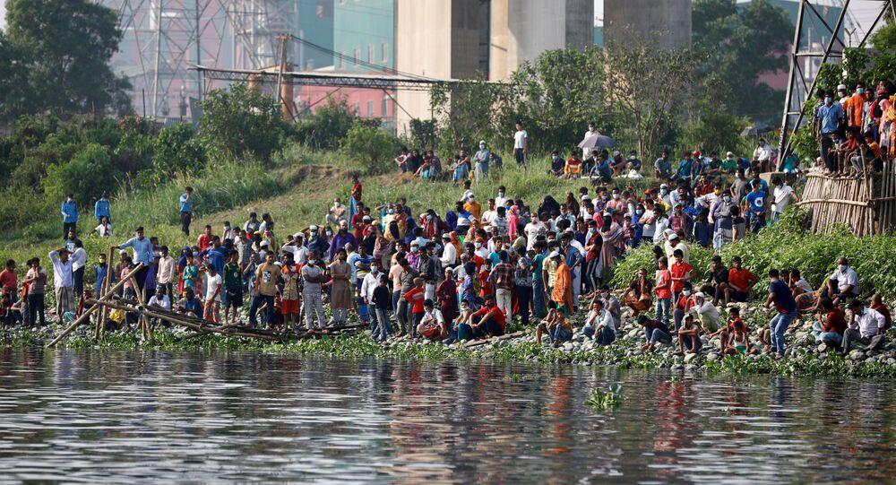 Pessoas se aglomeram na margem do rio Shitalakhsyaa, em Narayanganj, Bangladesh, após naufrágio de uma barca neste domingo, 4 de abril de 2021