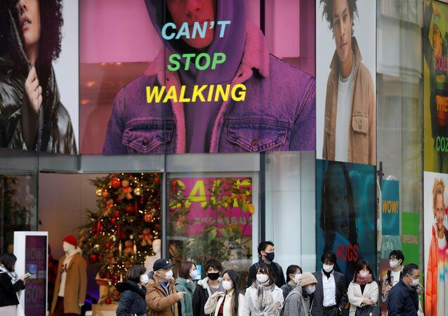 Pessoas usam máscaras protetoras em meio à pandemia do SARS-CoV-2 em Tóquio, Japão, 14 de dezembro de 2020