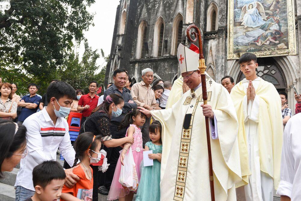 Bispo saúda católicos depois da missa do Domingo de Páscoa em Hanói, Vietnã, 4 de abril de 2021