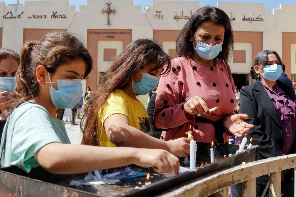 Pessoas acendem velas após a missa de Páscoa fora de igreja em meio à pandemia do novo coronavírus em Bagdá, Iraque, 4 de abril de 2021