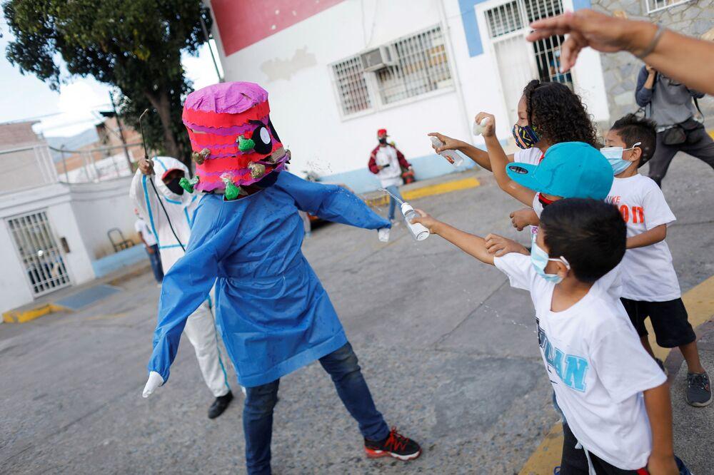 Crianças jogam álcool em gel em uma pessoa fantasiada de coronavírus durante a queima tradicional de Judas como parte das celebrações da Semana Santa em Caracas, Venezuela, 4 de abril de 2021