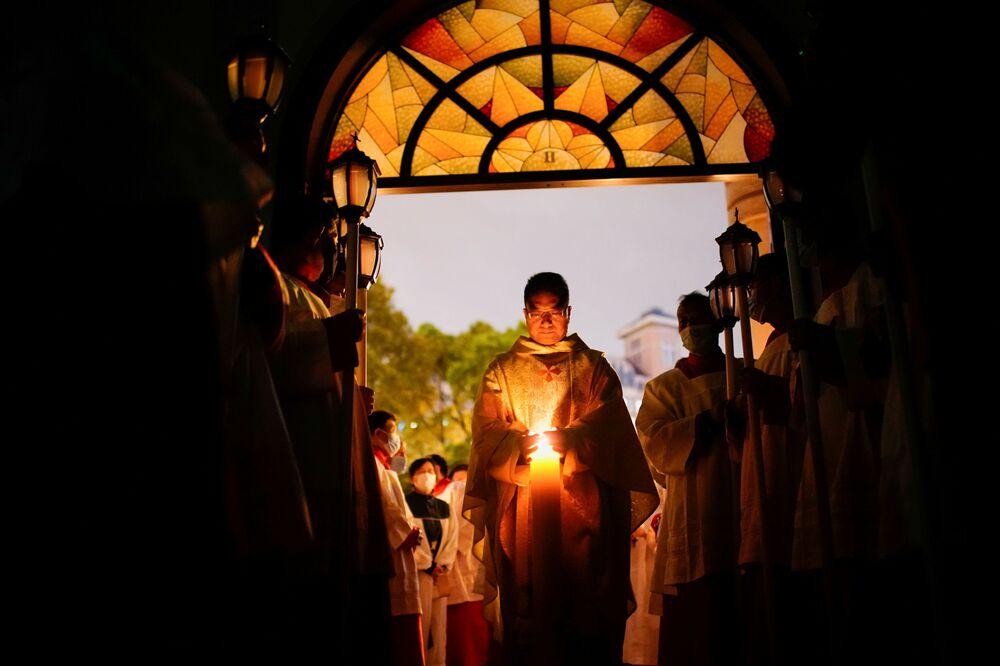 Católicos chineses  participam da Vigília pascal em igreja católica de Xangai, China, 3 de abril de 2021