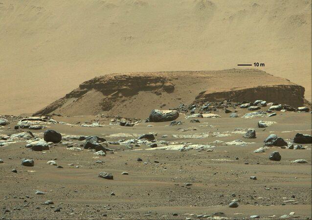 Alto afloramento de rocha, com depósitos de sedimentos em camadas a distância, mostrando um remanescente de um antigo delta de rio há muito desaparecido na cratera de Jezero, Marte, 5 de março de 2021