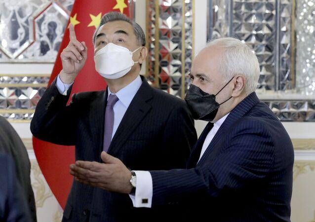 O ministro das Relações Exteriores iraniano, Mohammad Javad Zarif, à direita, dá as boas-vindas ao ministro das Relações Exteriores da China, Wang Yi, no início de sua reunião, em Teerã, Irã, sábado, 27 de março de 2021