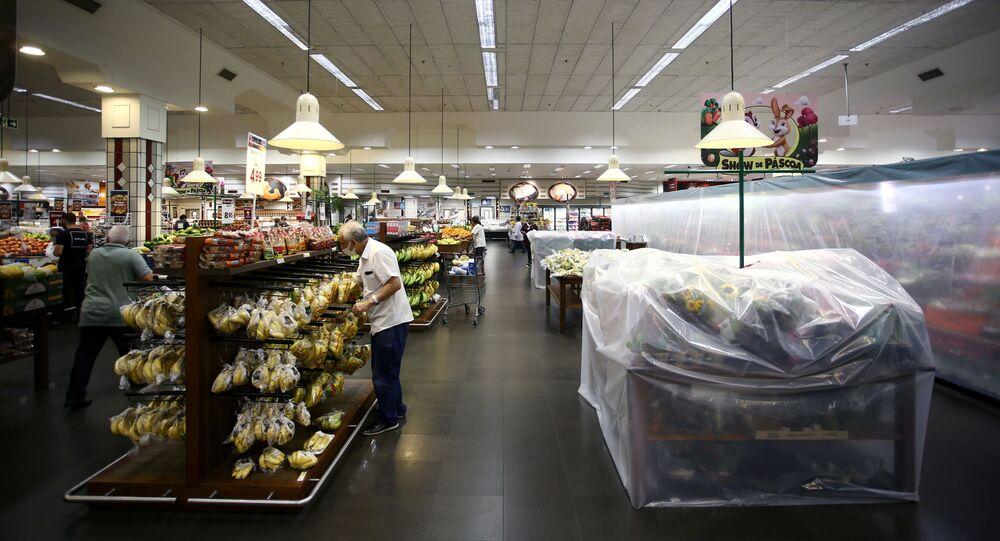 Cliente perto de prateleiras cobertas de plástico para ocultar produtos não essenciais proibidos para venda em supermercado devido às restrições da COVID-19, Porto Alegre, Brasil, 9 de março de 2021