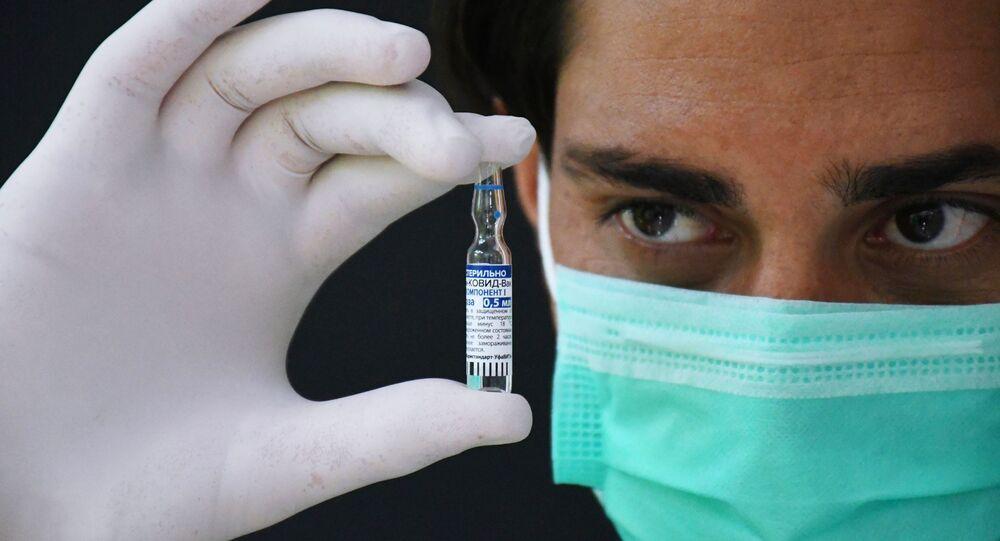 Em um ponto de vacinação de Karachi, no Paquistão, um profissional de saúde segura um frasco da vacina russa Sputnik V contra a COVID-19, em 5 de abril de 2021
