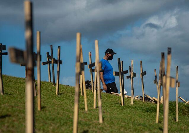 Em ato simbólico, manifestantes homenageiam os 330 mil mortos pela COVID-19 no Brasil com 330 cruzes colocadas no Morro do Cristo, em Salvador, na Bahia, no dia 3 de abril de 2021