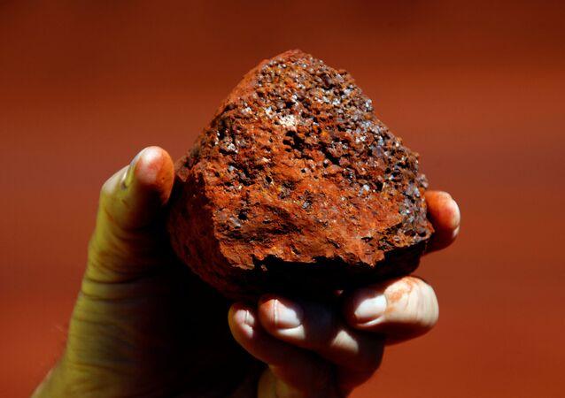 Um minerador detém um pedaço de minério de ferro em uma mina localizada na região de Pilbara, no oeste da Austrália, 21 de março de 2021