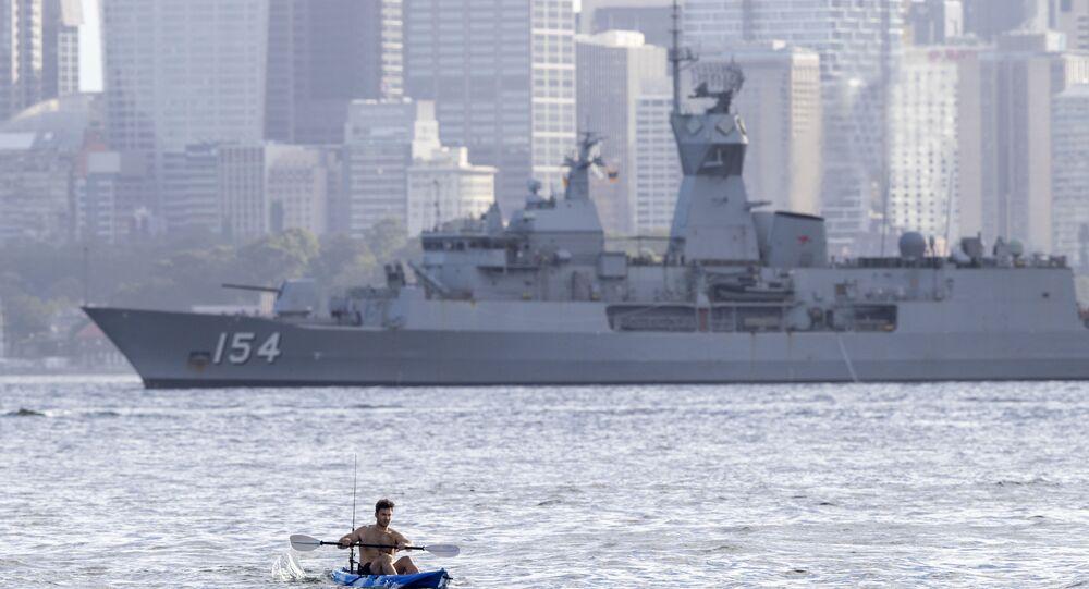 Homem rema em um caiaque tendo ao fundo o navio de guerra australiano HMAS Arunta